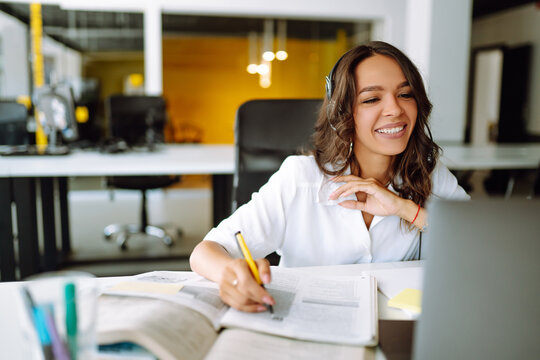 Young woman student wear wireless headphone study online. She learn language listen lecture watch webinar write notes look at laptop, distant education. Video call self-isolation during ncov situation
