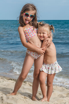 holidays with children near the ocean. Two little blonde girls stand embracing on a sea background on a sandy beach in a sunny city. children play on the sand and sunbathe