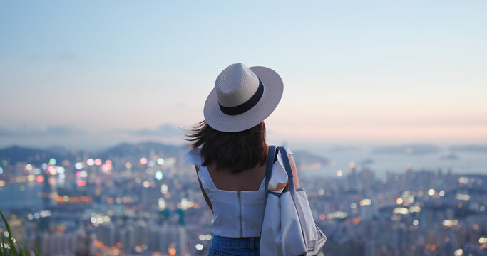 Woman look at the beautiful city view at sunset