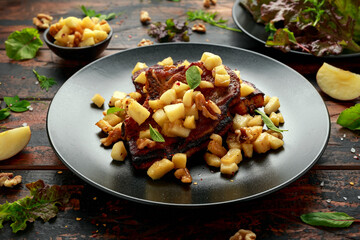 Roasted Pork chops with caramelized apples, walnuts and sage in black plate on wooden table