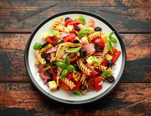 Antipasto salad with pasta, tomato, olives, red onion, bell pepper, salami, cheese artichoke and basil on wooden table
