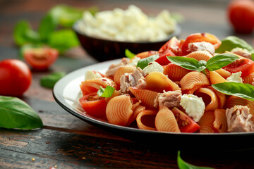 Conchiglie Tuna pasta with tomato sauce, feta cheese and basil on wooden table. healthy food