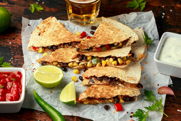 vegetarian mexican black beans tomato cheese and corn quesadilla served with cold beer salsa and yogurt dip sause on dark wooden background. healthy food