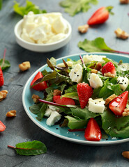 Goats cheese and strawberry summer salad served with nigella and sesame seeds drizzled with runny honey