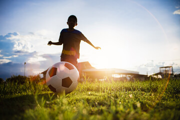 Boy kicking a ball while playing street soccer football on the green grass field for exercise. Outdoor sport activity for children and kids concept photo with copy space.