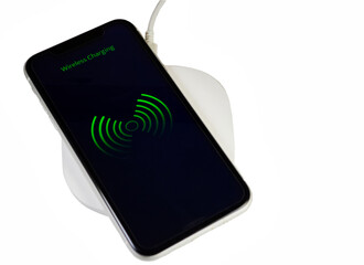 Smartphone charging on a wireless base with white background