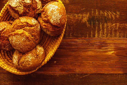Fresh bread rolls in basket on wooden table