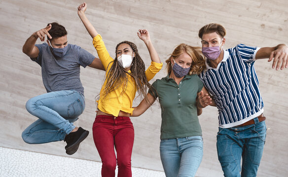 Young friends dancing together while wearing face mask outdoor - Happy people having fun in city after corona virus quarantine - Youth millennial generation friendship and health care concept