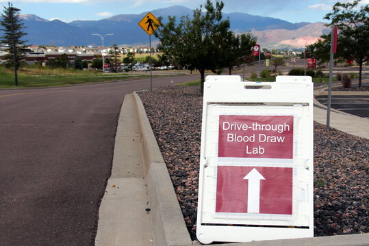 Covid-19 Drive Through Testing Lab Site Sign with Pikes Peak Mountain in the Background