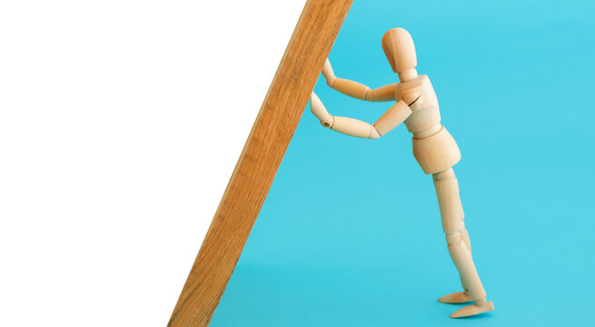 Wooden mannequin leans holding the wall. Support concept.