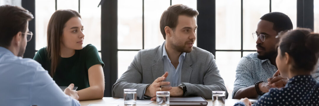 Wide image confident businessman speaking, sharing opinion, discussing project at corporate meeting with diverse colleagues, sitting at table in boardroom, leader business coach training staff