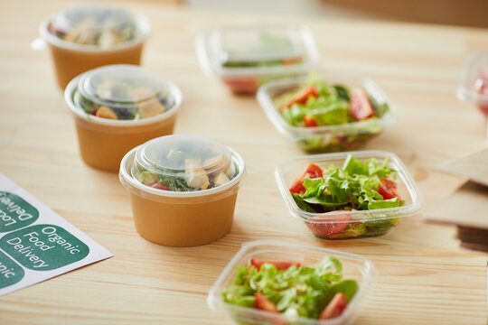 Background image of healthy food portions ready for packaging on wooden table in small food delivery service, copy space