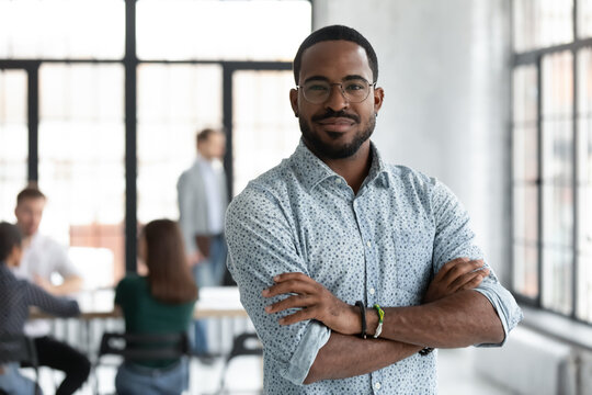 Head shot portrait confident young African American businessman wearing glasses looking at camera, successful executive startup founder standing in modern office room with arms crossed