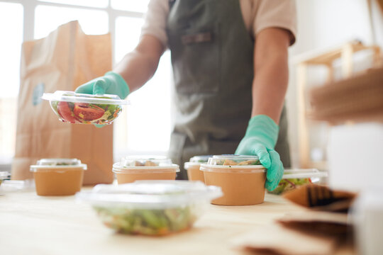 Close up of unrecognizable female worker wearing protective gloves while packaging orders at food delivery service, copy space