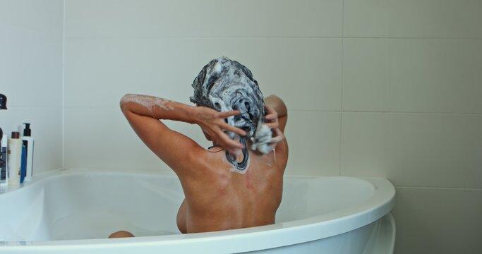 Beautiful woman taking bath at her bathroom. Washing her hairs.