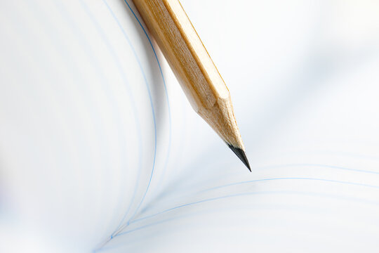 Closeup of sharp graphite pencil on white paper of notebook.  Concept of The National Day of Knowledge or International literacy day.