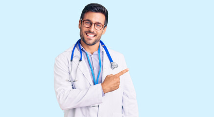 Young hispanic man wearing doctor uniform and stethoscope cheerful with a smile on face pointing with hand and finger up to the side with happy and natural expression