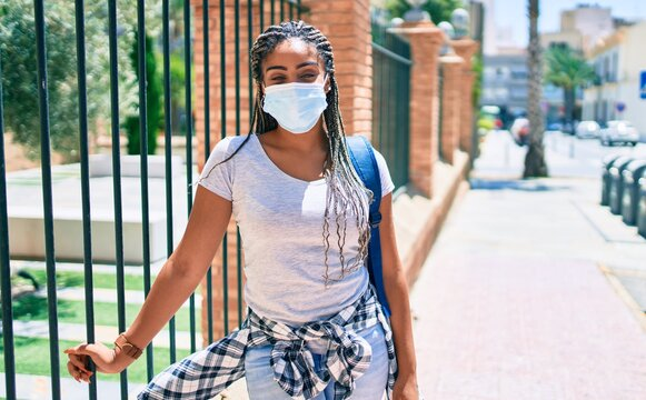 Young african american student woma wearing coronavirus safety mask at the university campus