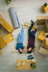 couple relax after unpacking boxes from house moving and relacation