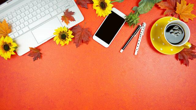 Autumn Fall Halloween Thanksgiving theme desktop workspace with laptop on stylish orange textured background. Top view blog hero header creative composition flat lay.