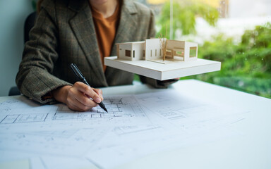 A female architect holding and working on an architecture house model with shop drawing paper in the office