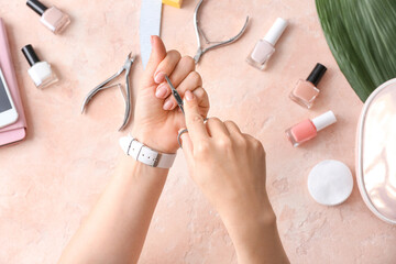 Woman doing manicure on color background