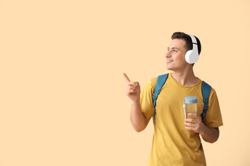 Young man with bottle of water and headphones pointing at something on color background