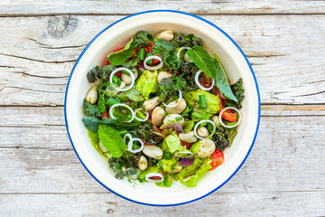 A healthy and delicious salad made from fresh vegetable leaves and broad beans. Vegetarian food.