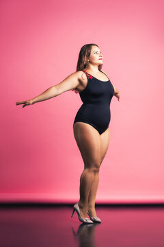 Plus size fashion model in black one-piece swimsuit, fat woman in lingerie on pink background