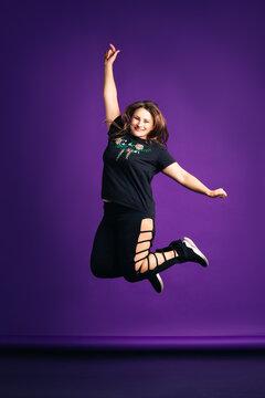Plus size model in sportswear jumping in studio, fat woman on purple background