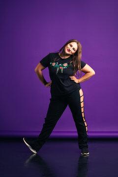 Plus size model in sportswear in studio, fat woman on purple background