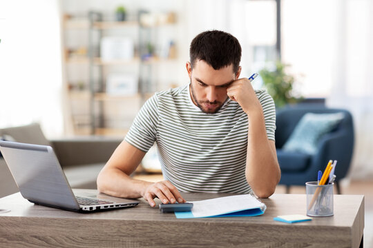 remote job and business concept - stressed man with papers, calculator and laptop computer working at home office