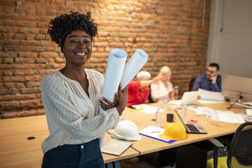 Black female architect smiling in busy office. Female Architect with Blueprints. Portrait of...