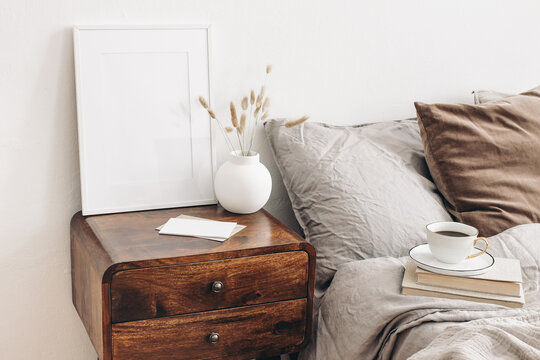 Portrait white frame mockup on retro wooden bedside table. Modern white ceramic vase, dry Lagurus ovatus grass. Cup of coffee and books in bed. Beige linen pillows in bedroom. Scandinavian interior.