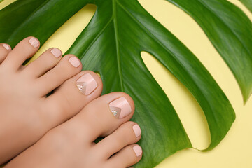 Female feet with pink nail design. Pink nail polish pedicure on yellow background.