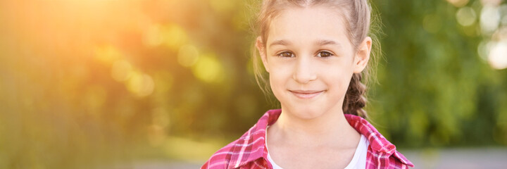 Funny young girl at park. Finish lockdown. Smile spanish person. Schoolgirl portrait. Summer female portrait. Face. Attractive lifestyle. Pretty kid. Looking at camera. Horizontal banner. Copyspace