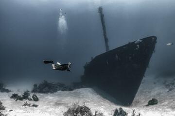 Scuba diver underwater with shipwreck