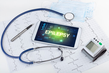 Tablet pc and medical stuff with EPILEPSY inscription, prevention concept