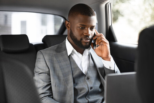Young african businessman using mobile phone and laptop in car