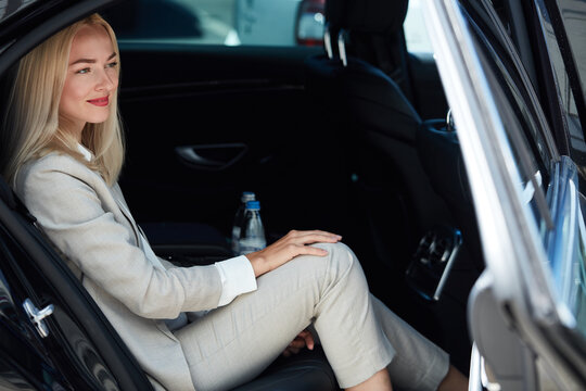 confident business woman inside of car, elegant blonde lady feel safety and comfort, in luxurious taxi