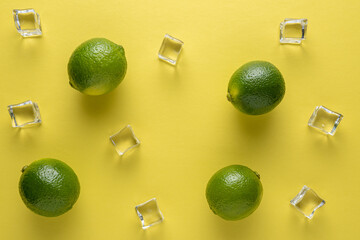 Limes with ice cubes on a bright background. Summer concept.
