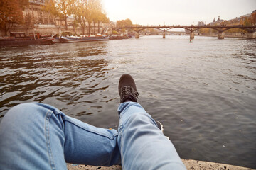 Man sitting on Pont Neuf, Paris, France.