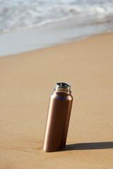aluminum reusable water bottle on the beach