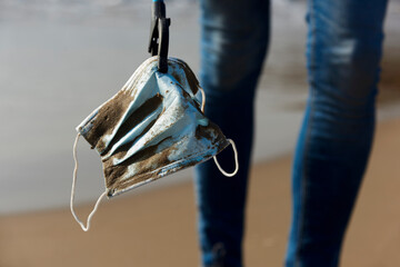 collecting a used surgical mask on the beach
