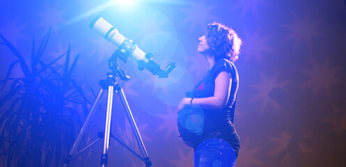 Pregnant woman looking at the stars through a telescope- astrology concept, horoscope predictions about the baby.