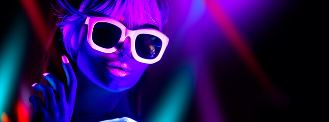 Disco girl in neon light dancing in night club. Fashion model woman. Closeup portrait of beautiful girl with fluorescent make-up. Body Art design in UV. Sunglasses. Colorful make up