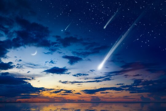 Amazing heavenly image with beautiful glowing sunset, comet and shooting stars, rising crescent moon and bright stars above sea.