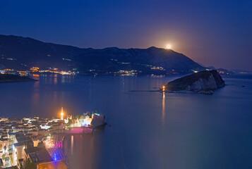 Full moon rise above Budva old city, Saint Nicholas island and Adriatic littoral, night cityscape, Montenegro, Europe. Famous tourist landmark and destination. Ričardova glava beach airview.