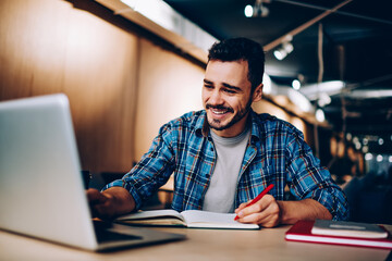 Cheerful hipster guy watching funny movie online and laughing from jokes while sitting in university campus and spending time for e learning and making research of information for course work