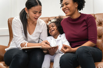 LGBT diversity Lesbian Couple Moments Happiness with her african girl laughing and drawing picture